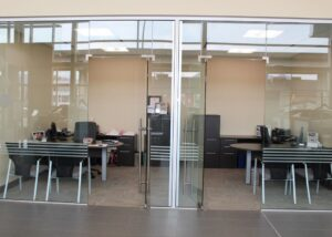 Glass walls for interiors in a Canadian car dealer with Unica hydraulic hinges.